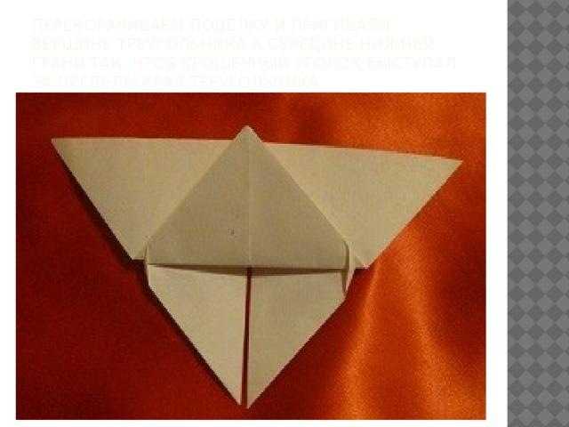 переворачиваем поделку и пригибаем вершину треугольника к середине нижней грани так, чтоб крошечный уголок выступал за пределы края треугольника